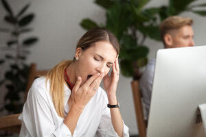 Woman yawning at her desk