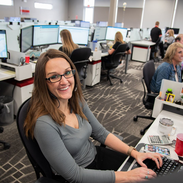 Granite Logistics employee sitting at desk smiling at photographer