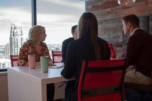 four Granite Logistics employees sitting at a table talking