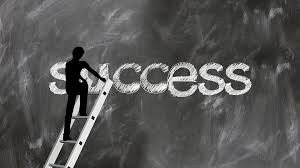 chalkboard image of the word success written by figure on ladder